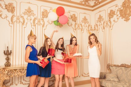 Cheerful pretty girls holding balloons and presents showing birt