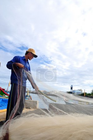 Quang Ngai, Vietnam - July 31, 2012: A fisherman is removing anchovies fish from his fishing net to begin a new working day in Ly Son island