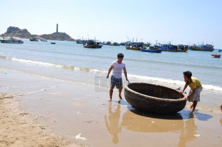 Lagi, Vietnam - February 26, 2012: Local fishermen are preparing their basket boat for a new working day in the Lagi beach
