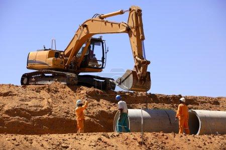 Photo pour Excavatrice aidant les travailleurs à poser des tuyaux en béton sur un chantier de construction - image libre de droit