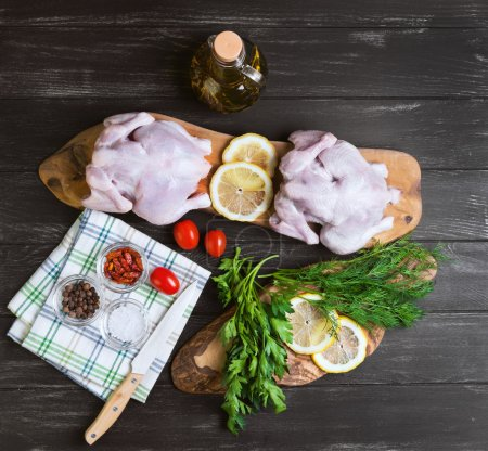 Photo for Two raw chicken carcasses, cherry tomatoes, dill, parsley, pepper, salt crystal, cutting board, bottle of olive oil on a wooden background in rustic style, top view - Royalty Free Image