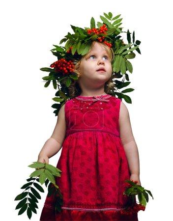 Photo pour Petite fille avec une couronne de brindilles et des fruits de frêne de montagne sur sa tête et des branches de Rowan dans leurs mains levant les yeux et souriant - image libre de droit