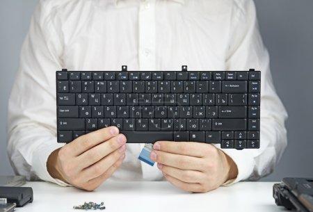 Photo pour Homme en robe blanche assis à une table avec un ordinateur portable et démonté tient un clavier d'ordinateur portable - image libre de droit