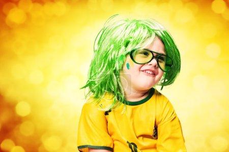 Photo pour Jeune garçon heureux, fan de football, dans des lunettes habillées en chemise nationale de football du Brésil - image libre de droit