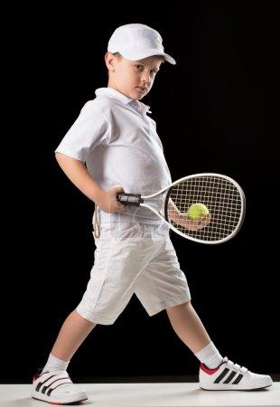 boy with tennis racket in studio