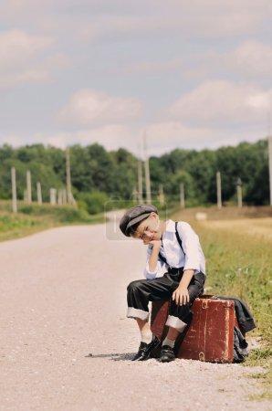 Photo pour Un jeune garçon assis sur une valise près de la route attendant que quelqu'un l'emmène - image libre de droit