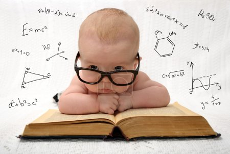 Photo for Funny portrait of cute baby in glasses lieing on old book and thinking of all the knowledge in the world - Royalty Free Image