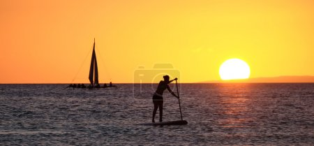 Silhouette of a girl floating on on the sup surfboard
