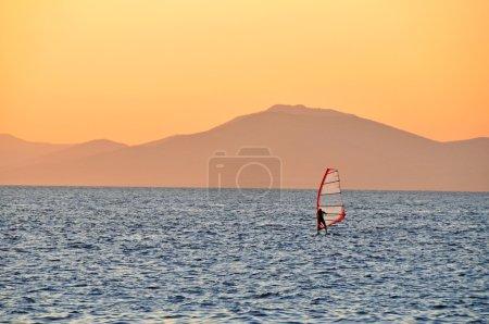 Windsurfer sailing on a sunset