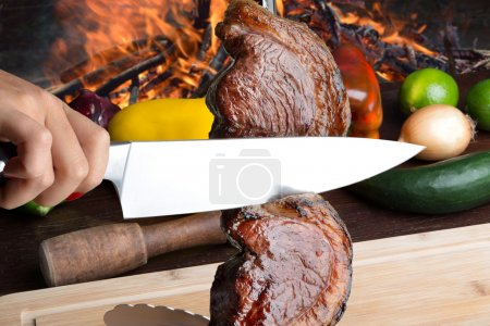 Photo for Female hands cutting picanha brazilian barbecue - Royalty Free Image