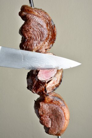 Photo for Knife cutting picanha brazilian barbecue - Royalty Free Image