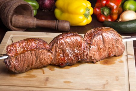 Photo for Brazilian barbecue - Roast meat on skewer with vegetables - Royalty Free Image