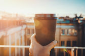 hands holding hot craft cup of coffee or tea in morning sunlight with view to blurred city background. Enjoy, lifestyle, take away breakfast concept. woman on the roof   drink
