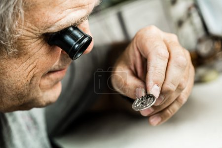 Clockmaker repairing  watch.
