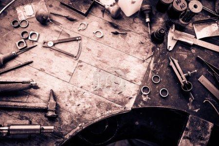 Photo pour Bureau de travail pour la fabrication de bijoux artisanaux avec des outils professionnels. Table en bois grunge. Vue d'en haut. Espace de copie . - image libre de droit