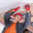 Builder attaches vapor barrier to wooden beams on ...