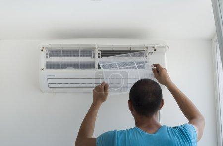 Foto de Hombre instala unidad interior de aire acondicionado - Imagen libre de derechos