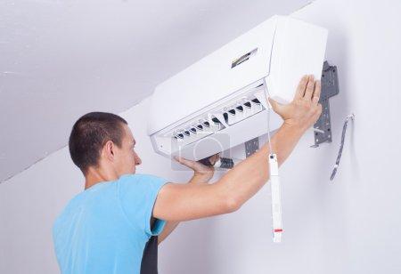 Photo pour Homme installe unité intérieure du climatiseur - image libre de droit