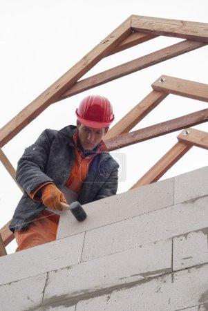 Photo pour Maçon pose le fronton des blocs de béton aéré - image libre de droit