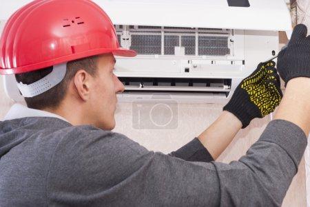 Photo pour Spécialiste nettoie et répare le climatiseur mural - image libre de droit