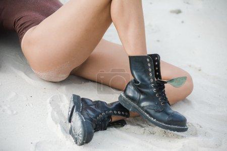 Photo pour Belles jambes féminines minces en bottes hautes en cuir. Fille avec des chaussures épaisses sur le sable - image libre de droit