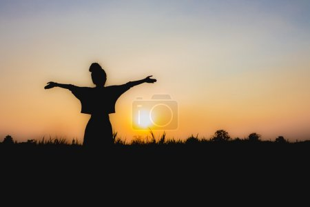 Photo for Silhouette of woman at sunset , Standing posture , near Dim atmosphere - Royalty Free Image
