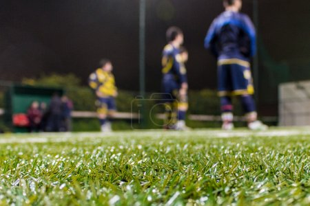 soccer team in the background listening to coach.