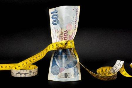 Photo pour La lire turque est serrée avec du ruban à mesurer. Crise de la lire turque. La lire turque va baisser et perdre du poids. L'économie turque plonge, s'effondre. Concept d'inflation, de dette et de tarifs. - image libre de droit