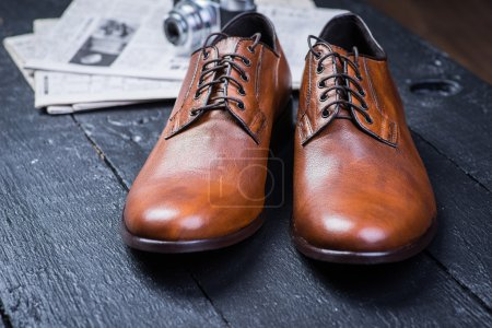 Brown leather shoes on black floor