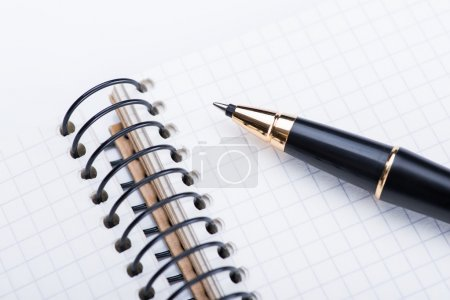 A spiral notebook with black ball pen on the white...