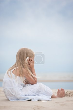 Beautiful young girl talking on the phone at the seaside