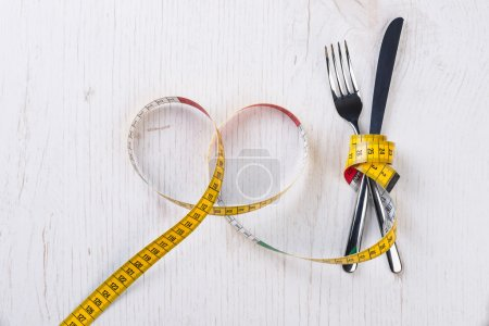 Fork and knife tied with metering tape on the wooden table