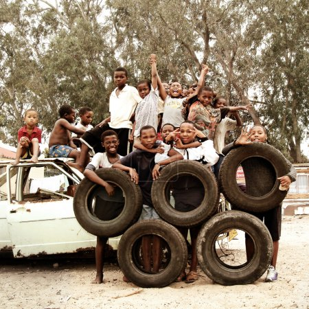 Children making Olympic Circles with tires in township, South Africa.