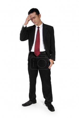 Photo for Full body shot of young Asian businessman standing and having a headache, isolated on white background - Royalty Free Image