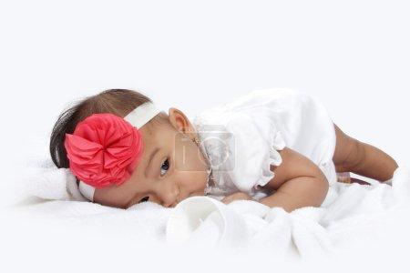 Foto de Cansado bebé tumbado en la cama con ojos soñolientos, aislado sobre fondo blanco - Imagen libre de derechos