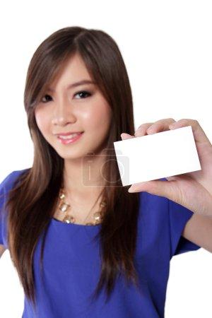 Photo pour Belle jeune femme asiatique avec de beaux yeux tenant la carte de visite vierge prête à l'emploi, isolée sur fond blanc - image libre de droit