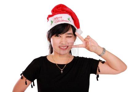 Photo pour Jeune adolescente asiatique dans le style de Noël clin d'oeil et souriant à la caméra avec pose mignonne, isolé sur fond blanc - image libre de droit
