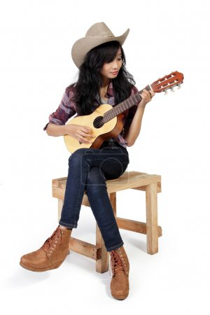 Cowgirl plays ukulele on a chair