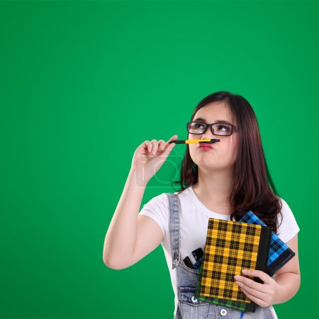 Cute nerdy girl look at the top of green background