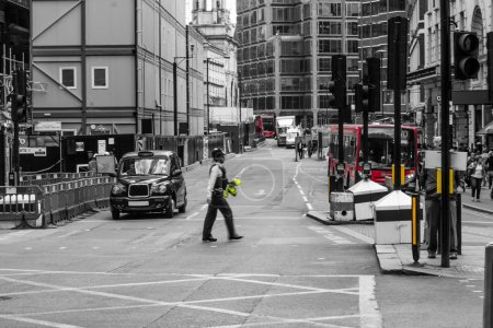 Photo pour Police officer crossing street, London, England, black and white photography - image libre de droit
