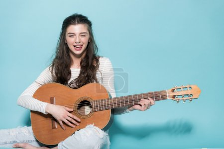 Beautiful young girl posing with guitar