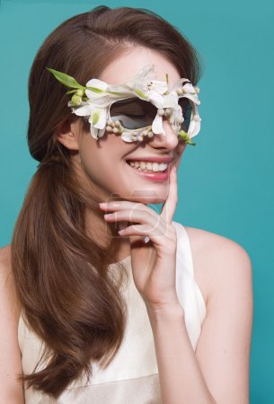 Fashion portrait of beautiful young lady with flowers sunglasses on blue background
