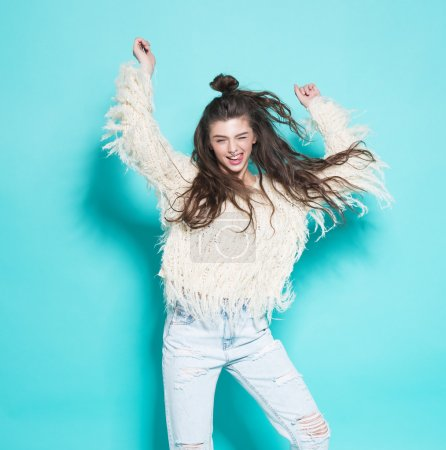 Photo for Studio portrait of cheerful fashion hipster girl going crazy making funny face and dancing. Blue color background - Royalty Free Image