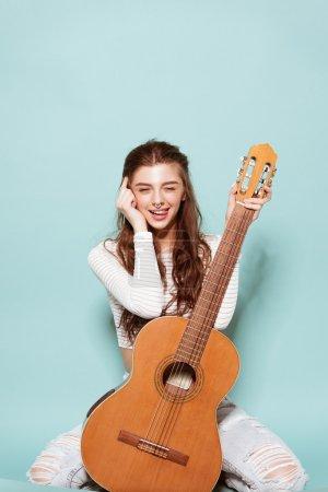 Photo pour Sourire belle jeune fille posant avec guitare - image libre de droit