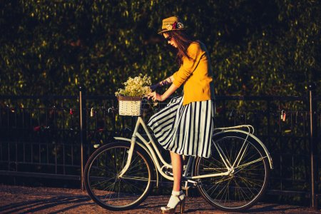 Young beautiful, elegantly dressed woman with bicycle. Beauty, fashion and lifestyle