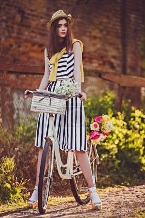 Photo for Hipster woman in dress on a bike in the village - Royalty Free Image