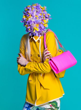 Fashion model in yellow coat and art accessories posing in the studio on blue background