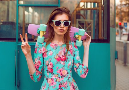 Photo for Beautiful hipster fashion young woman model posing with a pink skateboard on city background - Royalty Free Image