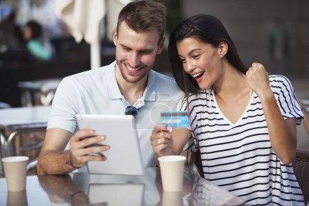 Couple buying online on holidays with a tablet and credit card on terrace bar