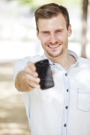 Happy man showing a mobile phone screen